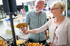 Shopping, food, sale, consumerism and people concept - happy senior couple buying fresh food stock photography