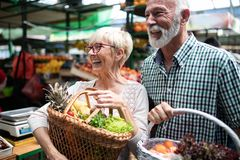 Shopping, food, sale, consumerism and people concept - happy senior couple buying fresh food stock images