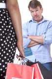 Shopping frenzy. Caucasian man with arms crossed looks with raised eyebrows at wife carrying shopping bags and credit card in hand and waits for explanation on stock photos