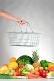 Shopping for fresh produce. A hand holds a wire shopping basket over a selection of fresh produce Stock Images