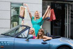 Shopping friends. Three shopping girl friends with car stock photography