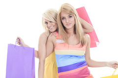 Shopping friends. Two Happy female shoppers smiling - isolated over a white background Stock Image