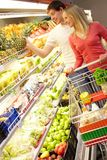 Shopping fruit. Portrait of man touching pineapple and woman with cart near by Royalty Free Stock Photography