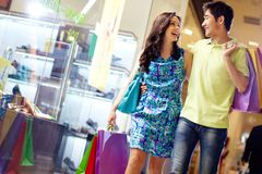 Shopping in full swing. Casually dressed beautiful couple walking through the mall carrying a lot of shopping bags Royalty Free Stock Image