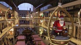 Shopping 'galleria av Berlin 'som dekoreras för jul med en stora träSanta Claus, upptaget med många shoppare stock video