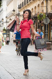 Shopping girl. Photo of a beautiful caucasian girl, wearing tight jean and high heels, is resting after shopping. There are passengers in the street Royalty Free Stock Image