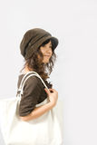 Shopping Girl. A cute young lady in brown skirt and hat with a white bag on shoulder, shopping Royalty Free Stock Photo