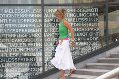 Shopping girl. Pretty blond girl walking down the stairs in a shopping area (text on the window is not a brand Stock Image