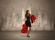 Shopping girl with bags in drawn city. An attractive young lady standing with red shopping bags in front of drawn city landscape silhouette concept Royalty Free Stock Photos