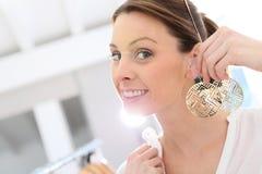 Shopping girl choosing earrings to buy Royalty Free Stock Images