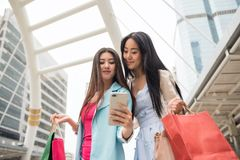 Shopping girl friends seflie in city. Beautiful Asian women friend selfie or take photo by smartphone or mobile phone with modern Bangkok city background after Royalty Free Stock Images