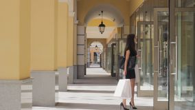 Shopping girl looking at shop windows chooses discount customer. Showcase stock video footage