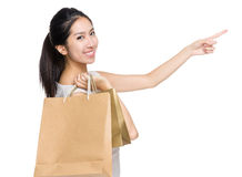Shopping girl with paper bag and finger point to aside Royalty Free Stock Image