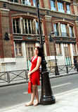 Shopping girl on a Paris street. A young woman in a red dress leaning on a light pole along a street in Paris with a shopping bag stock photography