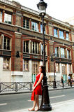 Shopping girl on a Paris street. A young woman in a red dress leaning on a light pole along a street in Paris with a shopping bag royalty free stock photos