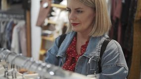Shopping girl. Portrait of a beautiful woman in the clothes store. Young blonde girl with red lips in a clothing store. Shopping girl. Portrait of the beautiful stock footage