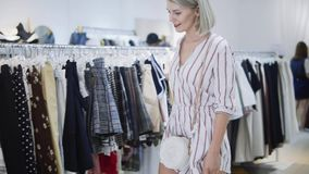 Shopping girl. Portrait of a beautiful woman in the clothes store. Happy blonde girl with red lips in a clothing store. Shopping girl. Portrait of the beautiful stock footage