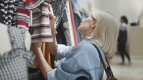Shopping girl. Portrait of a beautiful woman in the clothes store. Young blonde girl with red lips in a clothing store. Shopping girl. Portrait of the beautiful stock video footage