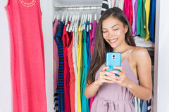 Shopping girl taking mirror selfie in home closet. Shopping girl taking selfie in mirror of changing room at store or home walk-in closet in bedroom. Asian woman royalty free stock photos