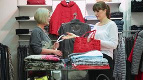 Shopping. Girlfriends choosing bags and clothes. Two pretty girlfriends choosing bags and clothes stock footage