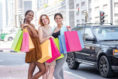 Shopping with girlfriends. Three keep shopping bags in their han Stock Photos