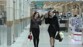Shopping. Girls after buying joyful out of the Department store in the Mall. Two attractive business lady walk around the Mall after shopping. Filmed in the stock footage