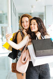Shopping girls making a selfie. Shopping girls full of bags making a selfie out of a shop royalty free stock images