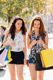 Shopping girls reading a mobile message Stock Image