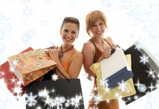 Shopping girls with snowflakes. Two happy girls with shopping bags and snowflakes Stock Image