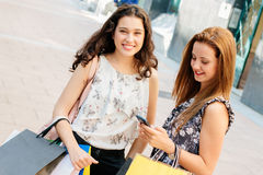 Shopping girls texting on phone Royalty Free Stock Photography