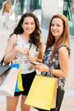 Shopping girls texting on phone Royalty Free Stock Photos