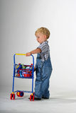 Shopping for groceries. Toddler boy filling toy shopping cart with groceries Royalty Free Stock Image