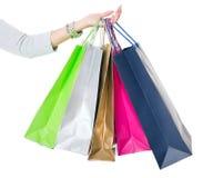 Shopping hänger lös Kvinnlig hand som rymmer färgrika shoppingpåsar på vit Fotografering för Bildbyråer