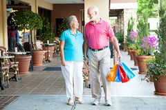 Shopping Hand-in-Hand. Senior couple shopping together at an outdoor mall, holding hands Royalty Free Stock Photos