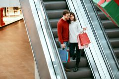 Shopping. Couple On Escalator In Shopping Center. Shopping. Happy Couple In Casual Clothes On Escalator In Shopping Center. High Resolution Royalty Free Stock Images