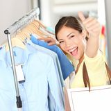Shopping - Happy shopper woman. Showing thumbs up excited holding shopping bag in clothing store looking for clothes on sale. Beautiful mixed race asian Royalty Free Stock Image
