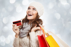 Shopping happy woman holding bags and credit card. Winter sales. Stock Photography