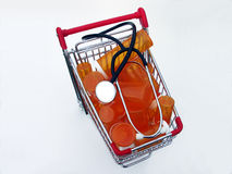 Shopping for health care (top view). Miniature shopping cart isolated on white filled with prescription bottles and a stethoscope illustrating shopping for a stock photos