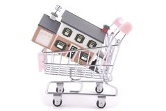 Shopping for a home. Miniature house in miniature shopping cart symbolizing home shopping royalty free stock photography