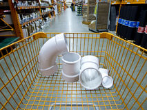 Shopping at a home improvement center. Shopping cart with plumbing supplies in a home improvement retail store Royalty Free Stock Image