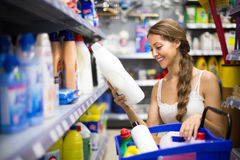 Shopping at household store. Positive smiling girl selecting detergents at the household store Royalty Free Stock Images
