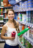 Shopping at household store. Smiling girl selecting detergents at the household store Stock Photography