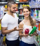 Shopping at household store. Smiling young couple selecting detergents at the household store Royalty Free Stock Image
