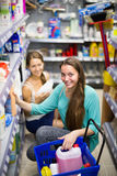Shopping at household store. Two joyful adult girls selecting detergents at the household store Stock Image