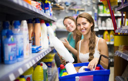 Shopping at household store. Two smiling adult girls selecting detergents at the household store Royalty Free Stock Photo