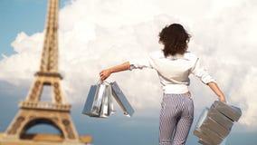 Shopping i Paris, modekvinna nära Eiffeltorn i Frankrike Ung kvinna som gör shopping i Paris Runt om världen turnerar den säsongs lager videofilmer