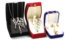 Shopping for jewelry. Golden jewelry sets inside open boxes, on white Royalty Free Stock Photos