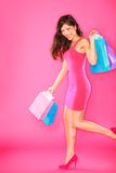 Shopping lady. Woman shopper holding shopping bags walking smiling happy and joyful in full length on pink background. Young beautiful mixed race Asian / Royalty Free Stock Photo