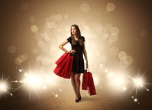 Shopping lady with bags in bright lights. A beautiful elegant woman in black standing with red shopping bags in front of brown background and bright glowing Royalty Free Stock Photos