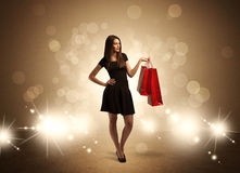Shopping lady with bags in bright lights. A beautiful elegant woman in black standing with red shopping bags in front of brown background and bright glowing Royalty Free Stock Photography
